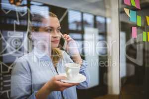 Businesswoman talking on phone during coffee break