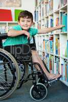 Elementary handicapped boy searching books in library