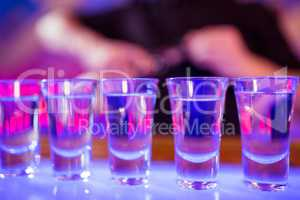 Shot glasses on illuminated bar counter