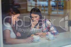 Cheerful women using digital tablet at coffee shop