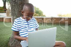 Elementary boy using laptop at park
