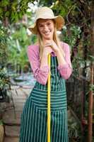 Portrait of happy gardener with work tool standing at garden