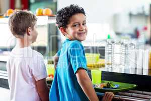 Schoolboy with classmate standing near canteen counter