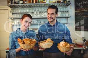 Portrait of cheerful baristas offering breads at coffee shop
