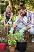 Male gardener planting with colleague at garden