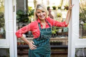 Mature woman standing at doorway in greenhouse