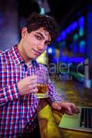 Portrait of man holding beer glass at bar counter
