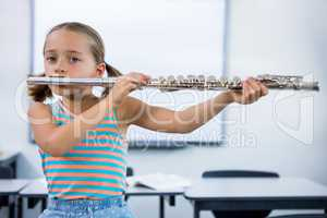 Portrait of elementary girl playing flute in classroom