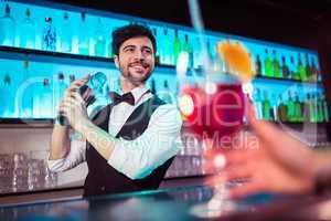 Barkeeper preparing cocktail for customer