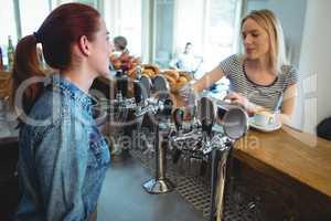 Barista talking with customer at cafe