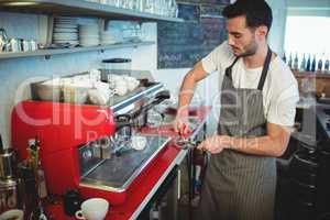 Handsome worker using strainer at cafe