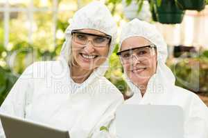 Smiling female coworkers wearing clean suit at greenhouse