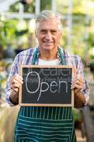 Happy mature owner holding open sign placard