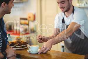 Barista giving coffee to customer at cafe