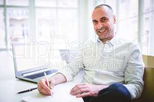 Smiling businessman writing document
