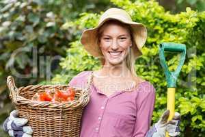 Female gardener holding tomato basket and work tool