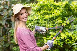 Happy female gardener pruning with clippers