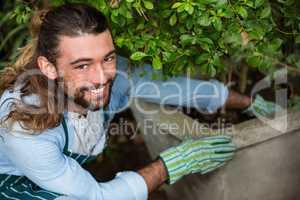 Portrait of happy worker planting at community garden