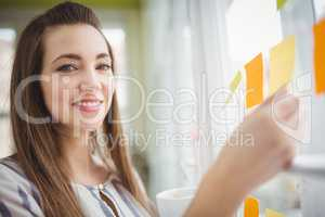 Portrait of businesswoman holding adhesive notes on window in cr