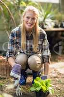 Confident female gardener planting outside greenhouse