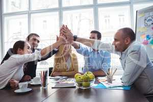 Coworkers giving high-five in meeting room
