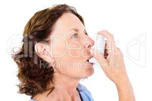 Close-up of mature woman using asthma inhaler