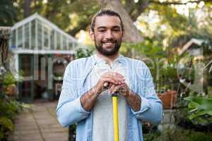 Portrait of happy gardener with work tool at garden