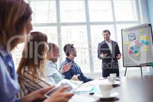 Coworkers looking at smiling businessman giving presentation