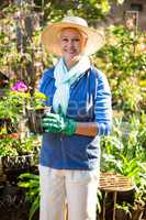 Portrait of confident gardener with potted plant at garden