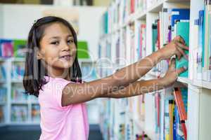 Portrait of girl searching books in school library