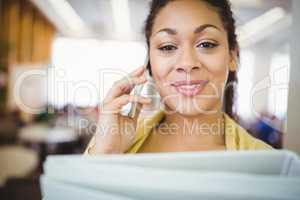 Portait of businesswoman holding files while using mobile phone