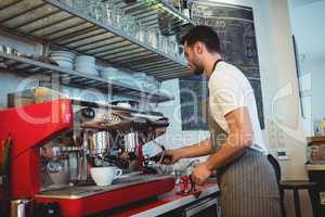 Side view of barista working by coffee maker at cafe