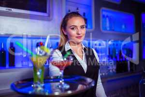 Portrait of confident bartender holding serving tray