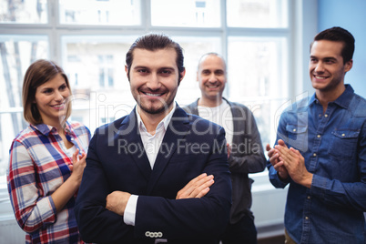 Coworkers clapping on businessman