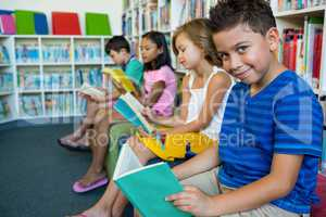 Elementary students reading books in library