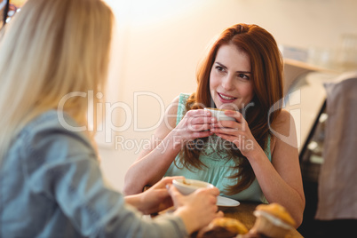 Happy woman listening to friend at coffee shop