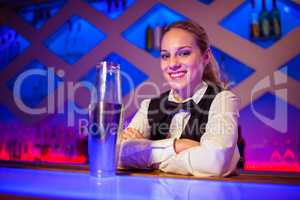 Confident barmaid sitting by cocktail shaker at counter