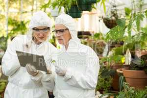 Scientists in clean suit discussing over digital tablet
