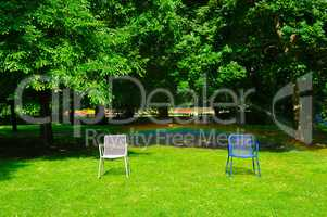 Summer park, green lawn, garden chairs and an automatic watering