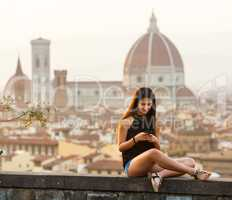 Teen at sunset in Florence uses the smartphone
