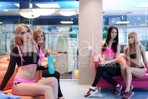 Beautiful girls resting before training in gym