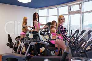 Girls training on simulators in fitness centre