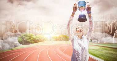 Composite image of successful businesswoman lifting a trophy