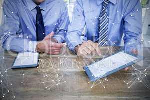 Composite image of businessmen using digital tablet at table