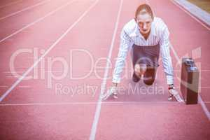 Composite image of concentrate woman in starting blocks