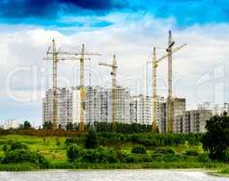 Horizontal contruction cranes on building site background