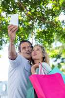 Couple making face while taking selfie in city