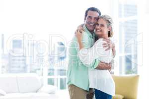 Mid adult smiling couple hugging at home