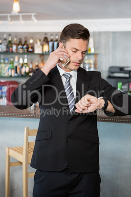Businessman checking time while talking on the mobile phone