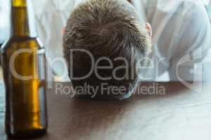 Depressed man with head down on a bar counter